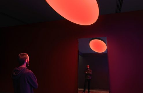 A photograph of a man standing in an installation artwork, within a red lit room and a light red orb like object appearing in the foreground, and again in a mirror reflection