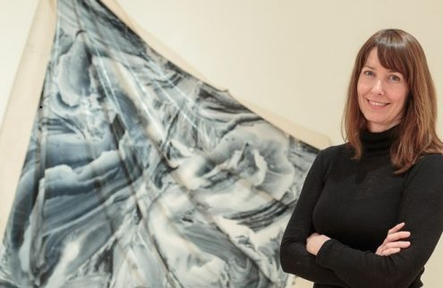 A woman stands smiling and looking directly into the camera in front of a hung textile artwork