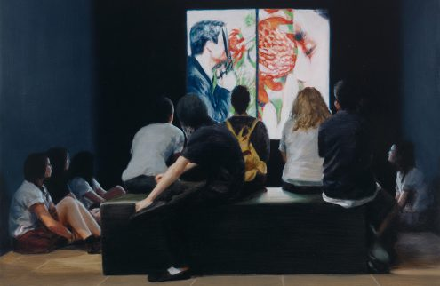 A group of people sit looking at an artwork in a dimly lit room