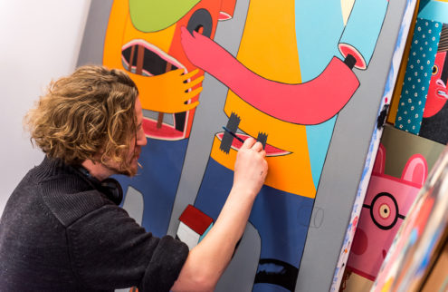 A man paints detail onto a colourful canvas