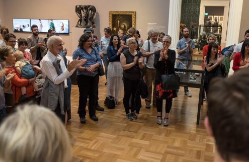 A group of people stand in a gallery space, applauding and listening to a speaker