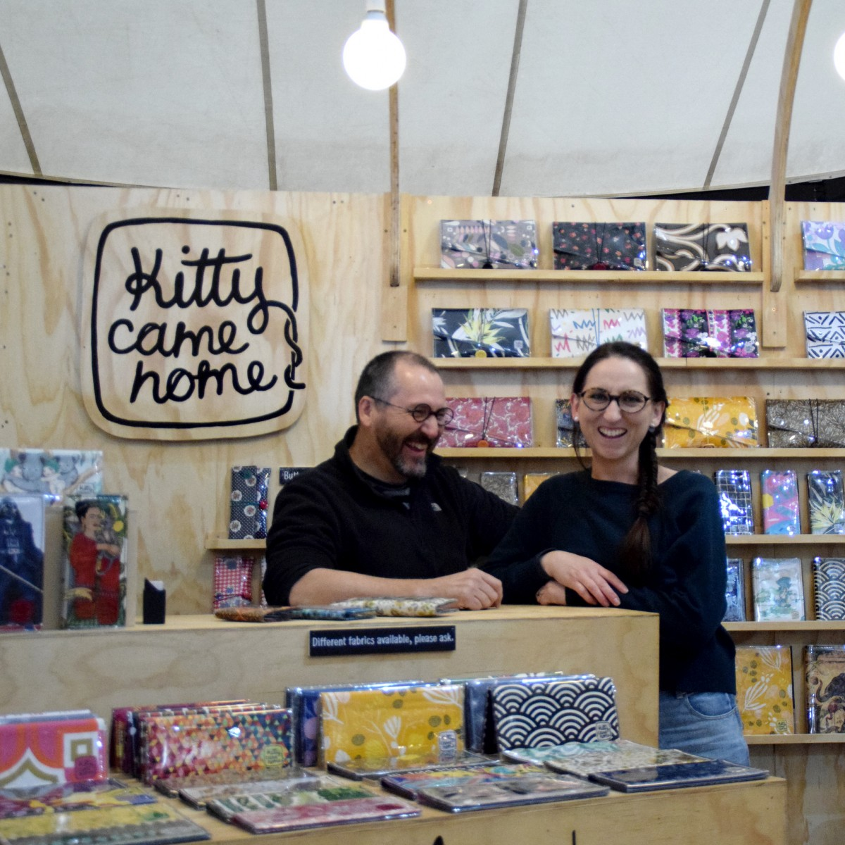 A photograph of a man and woman smiling, looking directly into the camera. In the background and foreground are collection of differently styled wallets and purses, In the left corner is a logo which reads' Kitty come home'