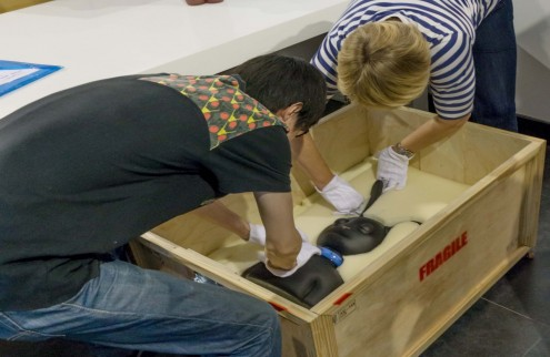 Two people help pack artwork into a crate after an exhibition