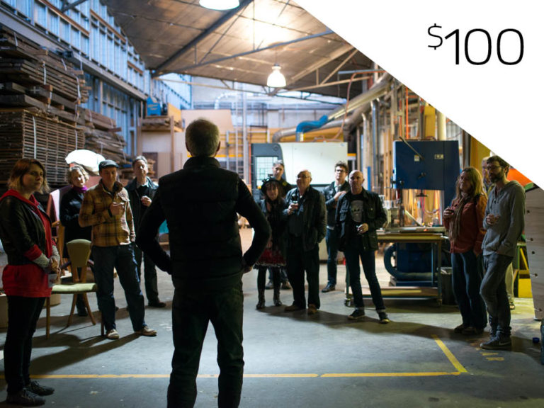 Person stands in front of a crowd of several other individuals in a warehouse environment, appears to be giving a speech