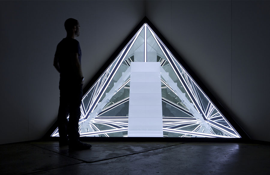 Silhouette of a person looking toward an illuminated pyramid shaped artwork