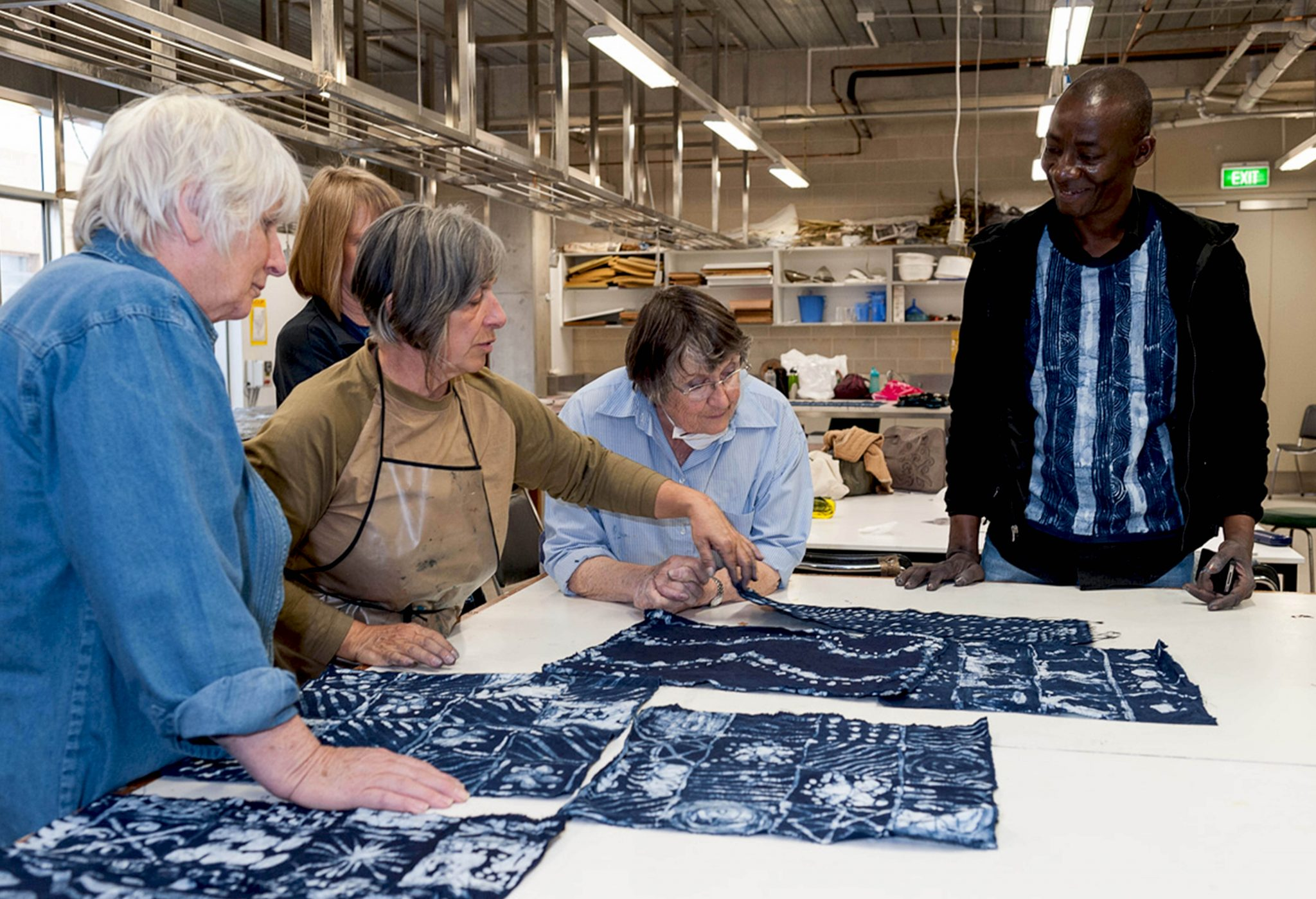 A group of five people standing around the table handling and looking at various dark blue textiles atop the table