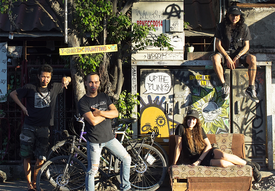 Four people sit and stand at an outside urban location with two cicycles, an old couch and tree.